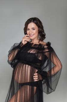 고립 된 검은 투명 실내에서 아름 다운 행복 한 임신 갈색 머리 여자