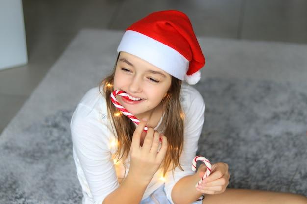 Красивая счастливая девушка в красной шапке санта-клауса ест полосатые рождественские леденцы