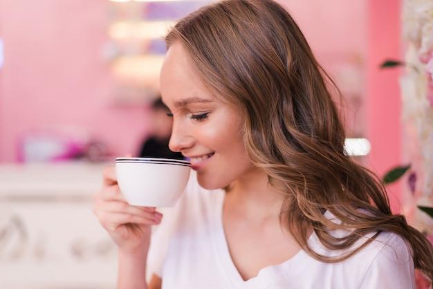 Красивая счастливая милая молодая женщина, сидящая в кафе.