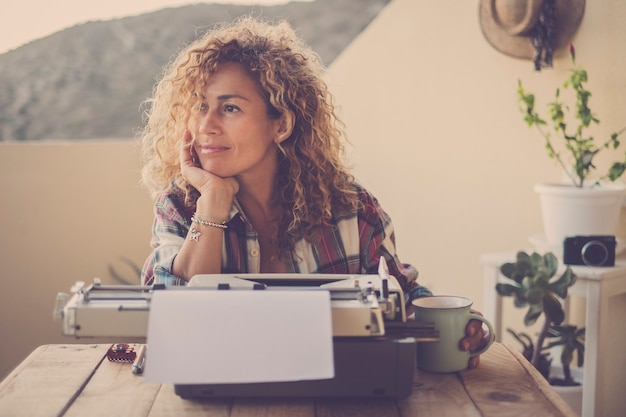 Beautiful happy relaxed middle age caucasian woman blonde curly hair taking a break and stop writing with her old typewriter
