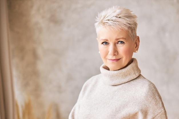 아늑한 스웨터와 짧은 머리를 입고 아름 다운 행복 한 은퇴 한 여자