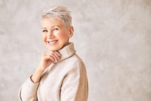 Красивая счастливая пенсионерка, одетая в уютный свитер и короткую прическу