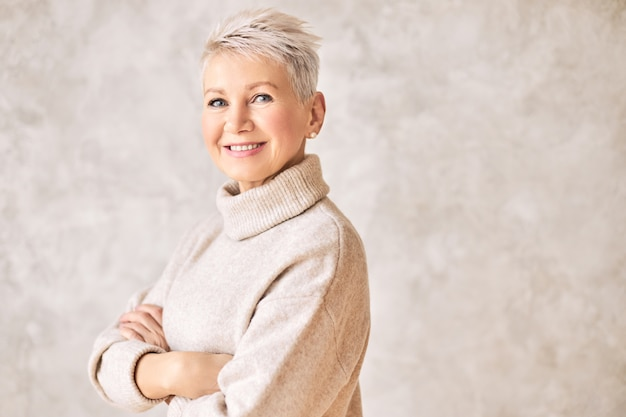 Beautiful happy retired woman wearing cozy sweater and short hairdo