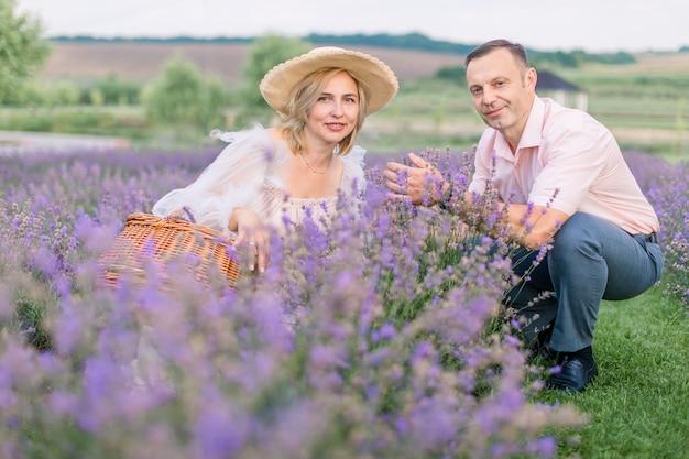 라벤더 밭에 앉아 카메라를 바라보는 아름다운 행복한 낭만적인 중년 부부