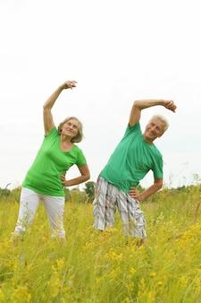 Красивая счастливая старшая пара делает упражнения в поле