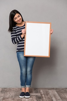 Beautiful happy smiling asian woman in striped jumper looking at front holding white frame