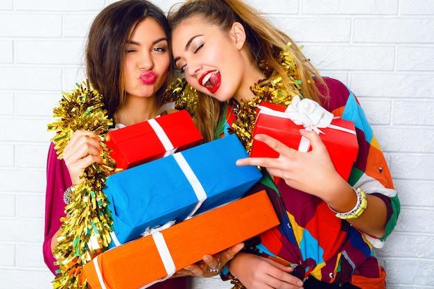 파티 선물 및 선물을 들고 아름 다운 행복 미소 가장 친한 친구. 트렌디 한 옷과 황금빛 반짝이를 입고
