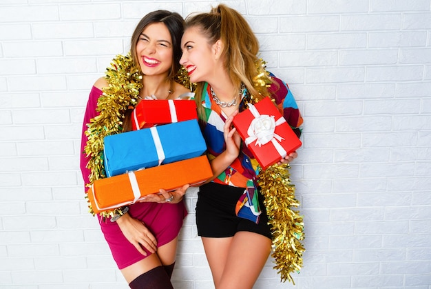 Beautiful happy smiling best friends holding party gifts and presents. wearing trendy clothes and golden tinsel