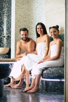 Beautiful happy smiling family in bath towels are looking on camera while relaxing in sauna or hammam. vacation and spa procedure