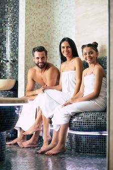 목욕 수건에 아름 다운 행복 한 미소 가족은 사우나 또는 터키 식 목욕탕에서 휴식을 취하는 동안 카메라를 찾고 있습니다. 휴가 및 스파 절차