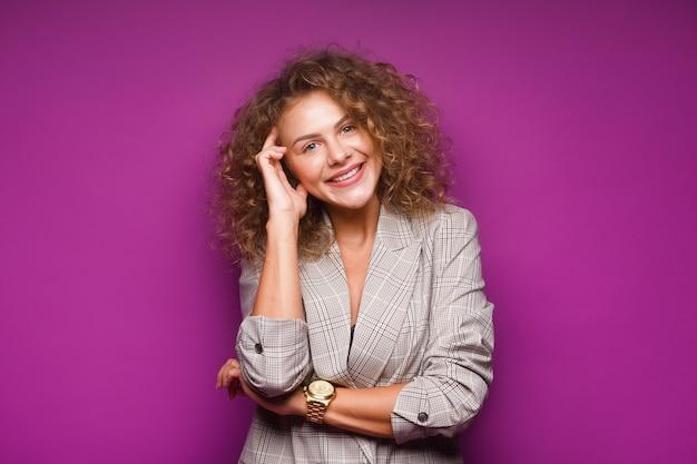 Bello modello femminile sorridente felice con l'acconciatura lunga di trucco di bellezza