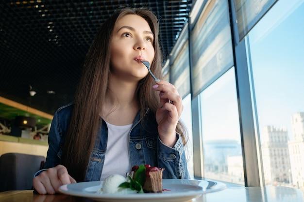 Красивая счастливая улыбающаяся девушка пробует десерт в кафе