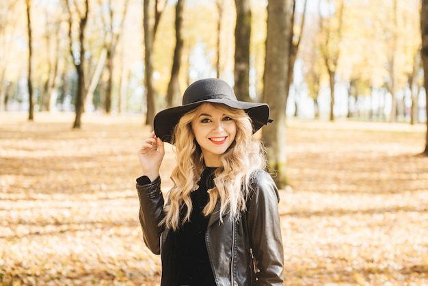 Beautiful happy smiling girl with long blonde hair, red lips, wearing stylish hat,  jacket posing in autumn street. outdoor portrait, day light. female autumn fashion concept.