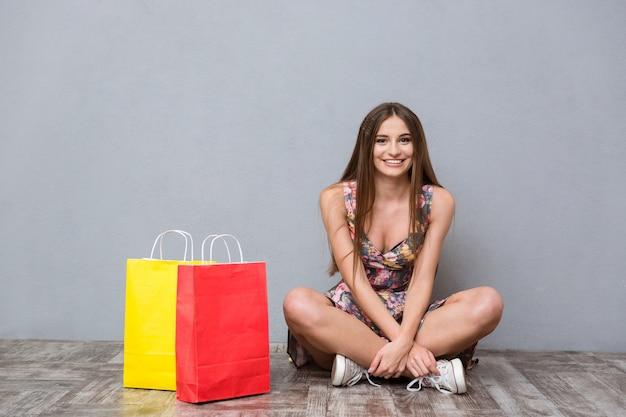 Красивая счастливая улыбающаяся девушка с длинными волосами в цветочной одежде сидит со скрещенными ногами на полу возле красных и желтых сумок