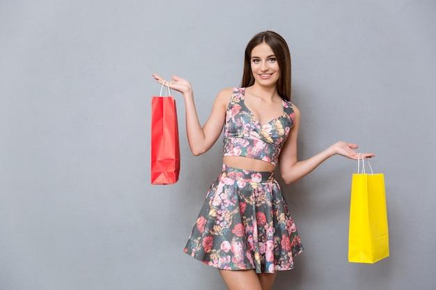 Красивая счастливая улыбающаяся девушка с длинными волосами в цветочной одежде с красными и желтыми сумками