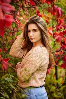 秋の通りでポーズをとって、長い髪の美しい幸せな笑顔の女の子。屋外の肖像画を閉じます。女性のファッションコンセプト。