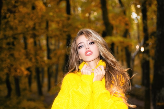 Beautiful happy smiling girl with long hair wearing stylish jacket posing in autumn day outdoor port...