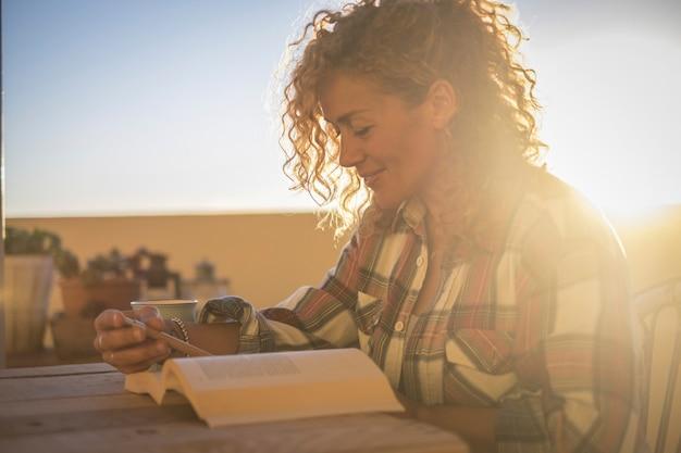美しい幸せな笑顔のリラックスした白人の巻き毛の金髪の女性が自宅の屋外テラスで日没を待っている本を読んで