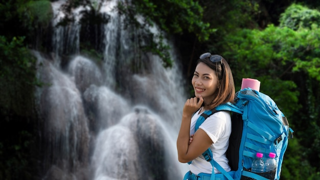 Beautiful happy and smiling tourist woman having fun with backpack on waterfall
