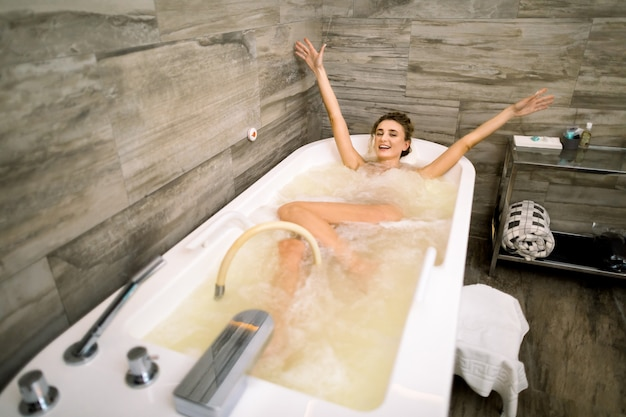 Beautiful happy smiling woman enjoying and relaxing in jacuzzi at the spa center, having professional hydro massage and holding arms up