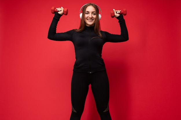 Beautiful happy smiling young brunet woman wearing black sport clothes isolated on red surface doing fitness using dumbbells wearing white bluetooth headsets listening to music looking at camera