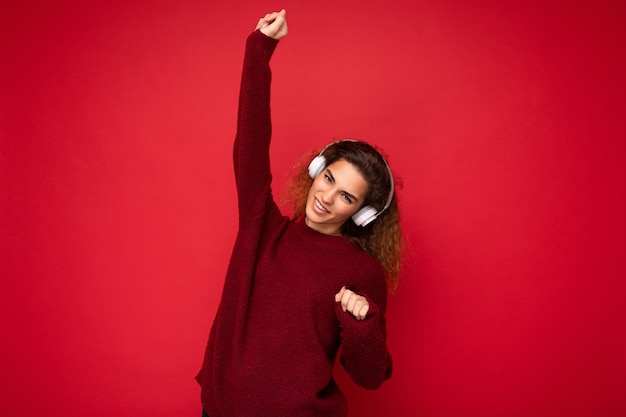 Beautiful happy smiling young brunette curly woman wearing dark red sweater isolated over red
