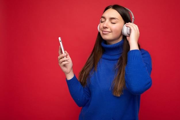 Красивая счастливая улыбающаяся молодая брюнетка женщина в синем свитере на красном фоне