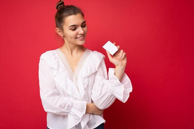 아름 다운 행복 하 게 웃는 젊은 어두운 금발 여자 플라스틱 카드를 보고 신용 카드를 들고 빨간 배경 위에 고립 된 흰색 블라우스를 입고. 복사 공간