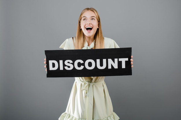 Beautiful happy smiling young woman with discount sign isolated over grey