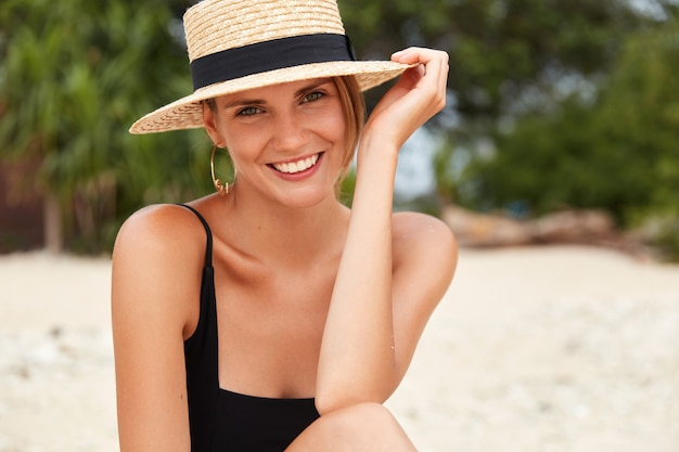 Beautiful happy smiling young woman with tanned slim body wears black bikini and straw hat, relaxes on beach paradise, sunbathes in tropical travel destination, enjoys summer vacations at ocean.
