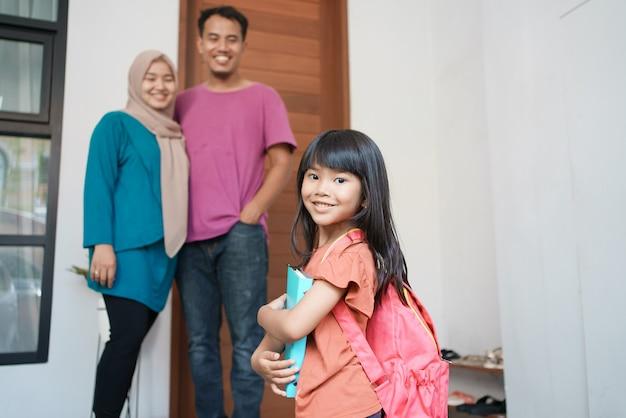 学校に行く準備をしながら笑顔の美しい幸せな学生と後ろのイスラム教徒の親