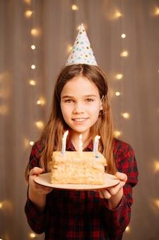 Красивая счастливая предназначенная для подростков девушка с праздничным тортом. традиция загадывать желание и задуть костер на вечеринке. день отдыха.