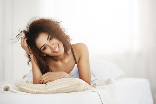 Красивая счастливая нежная африканская женщина лежа на подушке дома усмехаясь проснулась на солнечный день в утре.