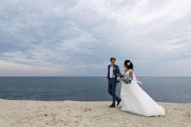 Beautiful happy wedding couple bride and groom at wedding day outdoors at beach