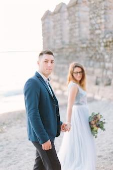 Красивая счастливая свадьба пара жениха в синем пиджаке и невеста в роскошном синем платье, ходить, держась за руки возле озера гарда. италия, сирмионе