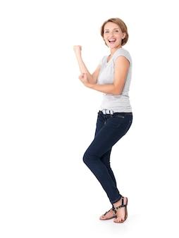 白で隔離されるダイナミックでエネルギッシュな表現で勝者であることの成功を祝う美しい幸せな女性