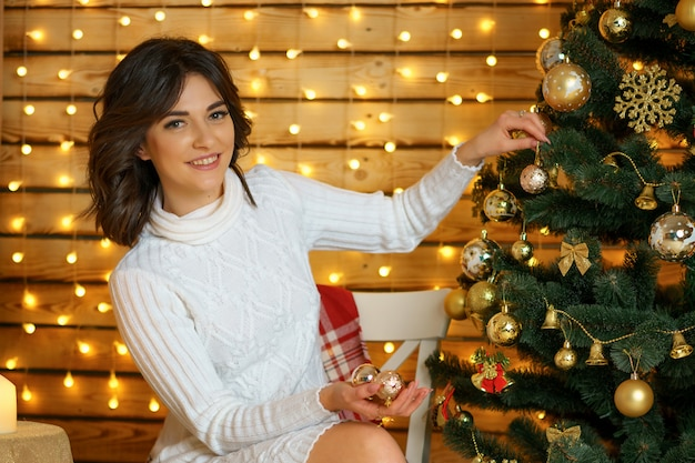 Beautiful happy woman dresses up christmas tree