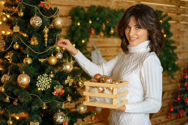 Beautiful happy woman dresses up christmas tree