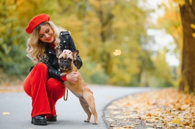 Beautiful and happy woman enjoying in park walking with her adorable french bulldog.