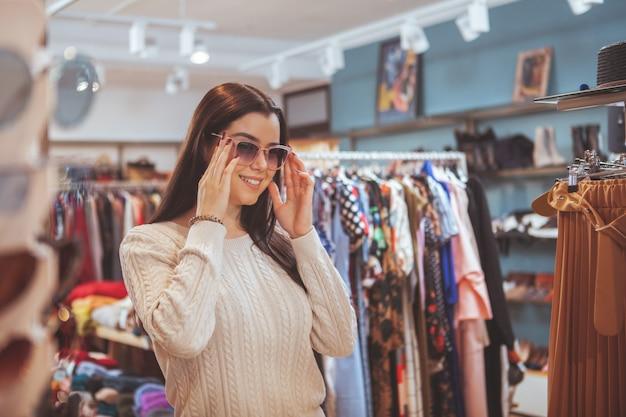 Beautiful happy woman enjoying shopping at clothing store