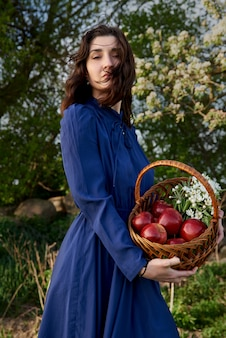 Beautiful happy woman in the garden holds a basket with red apples