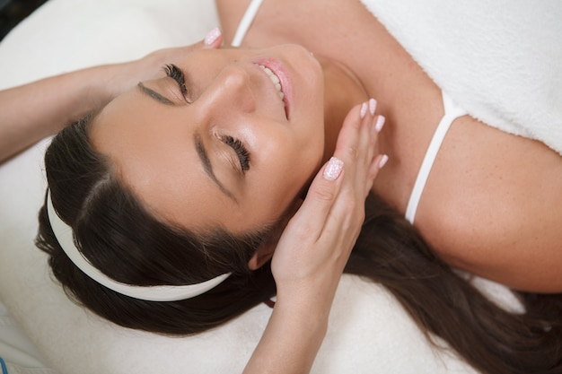 Beautiful happy woman getting face and neck massage at spa center