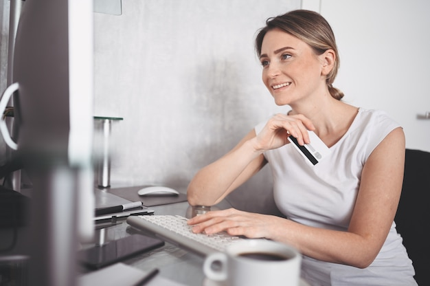 Beautiful happy woman holding credit card in hand and using laptop computer keyboard. businesswoman or entrepreneur working. online shopping, e-commerce, internet banking, spending money concept
