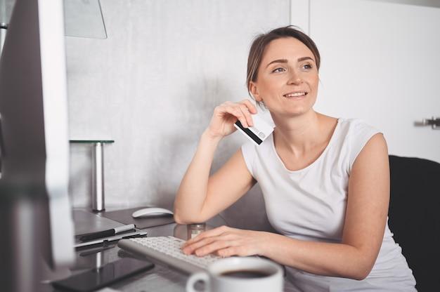 Красивая счастливая женщина держа кредитную карточку в руке и используя клавиатуру портативного компьютера. предприниматель или предприниматель работает. интернет-магазины, электронная коммерция, интернет-банкинг, концепция тратить деньги