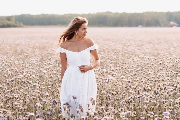 自然の中で夏の花のフィールドで白いドレスを着た美しい幸せな女性