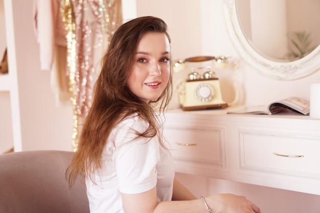 파티 핑크 탈의실 전에 포즈를 취하는 그녀의 화장대 근처 그녀의 방에서 아름다운 행복한 여자