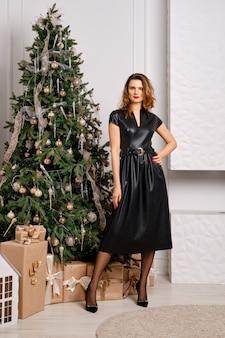 선물 상자 크리스마스 트리 근처에 서 가죽 드레스에 아름 다운 행복 한 여자