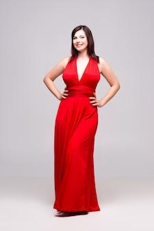Красивая счастливая женщина в красном платье на серой стене, портрет в полный рост