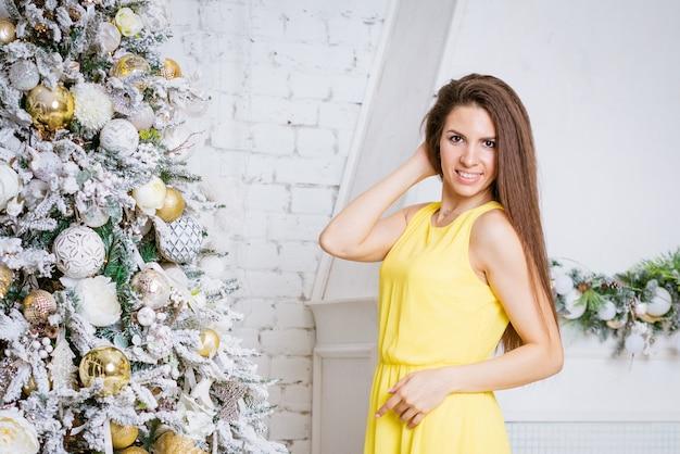 黄色のドレスを着た美しい幸せな女性は、自宅の明るいリビングルームで笑顔のクリスマスツリーのそばに立っています...