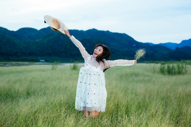 A beautiful, happy woman is throwing her hat on a beautiful meadow and there is a mountain in the .